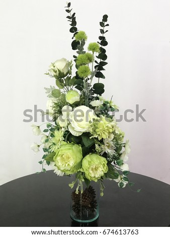 The beautiful flowers  in vase. The white flower with green leaves arranged in a clear vase. The seed dried of conifer put in the clear vase. #674613763