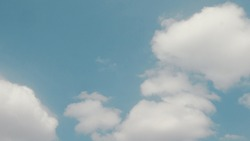 The beautiful fluffy shape of the cloud contrast with the blue deep sky in pastel color