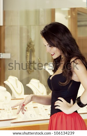 the beautiful girl chooses jewelry on a show-window of jewelry store