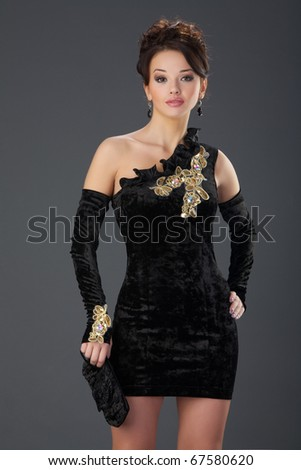 The beautiful girl in a black velvet dress with wavy hair.