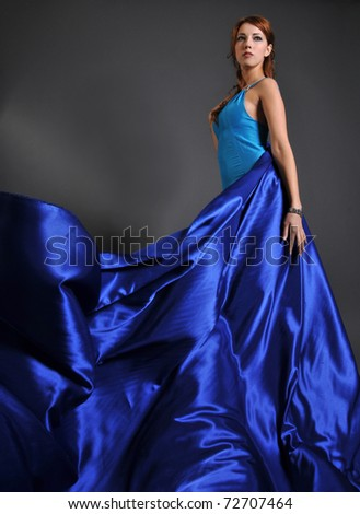The beautiful girl in a blue dress with fluttering fabrics