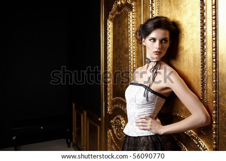 The beautiful girl in a dress at a gold door - stock photo