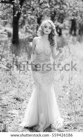 The beautiful girl in a garden, summer. The girl with beautiful ringlets and a make up in apple garden, spring. The girl in a beautiful dress walks in a garden and enjoys heat and sun #559426186