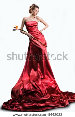 The beautiful girl in a long red dress holds an exotic flower in a hand