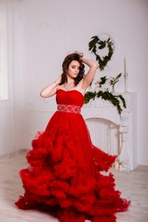 The beautiful girl in a long red dress posing in a vintage scene.Young beautiful woman wearing a red dress in the old hotel.Sensual elegant young woman in red dress and indoor shot.