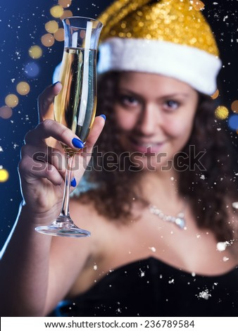 The beautiful girl in a New Year\'s Eve. Focus on glass and fingers. Low light