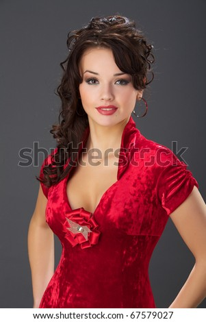 The beautiful girl in a red velvet dress with wavy hair.
