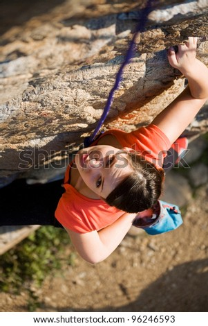 The beautiful girl is engaged in rock-climbing on a vertical rock