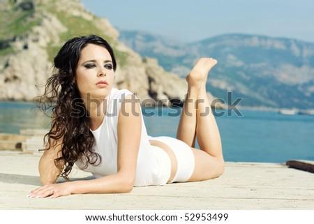 The beautiful girl lies on a pier near the sea