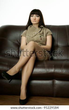 The beautiful girl on a leather sofa