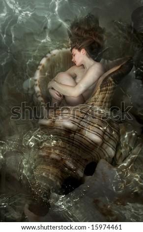 The beautiful girl sleeps in a sea cockleshell - stock photo