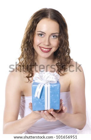 The beautiful girl smiling holds a gift in a box on a white background.