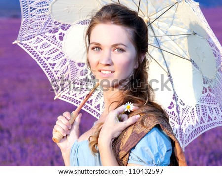 The beautiful girl walks with a white umbrella across the field of a lavender