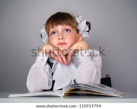 The beautiful girl with books sits at a school table fnd dreams - stock photo