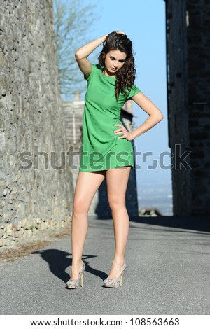 the beautiful girl with green dress walks in the ancient village of the castle