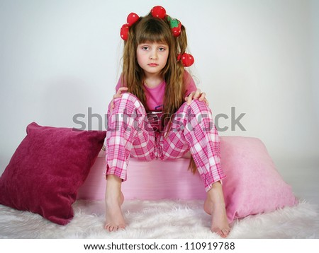 The beautiful girl with hair curlers sits on pillows