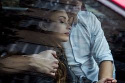 The beautiful guy and girl are sitting in the car, the reflection of the street on the glass of the car, the rainy weather, he gently embraces her, she closed her eyes. Love story