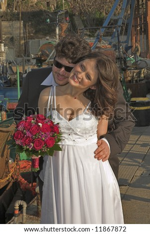 The beautiful, happy groom and the bride on wedding walk in ancient to port.