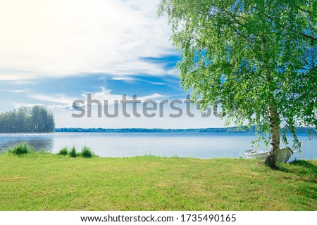 The beautiful landscape of a white simple wooden boat tied to a birch tree on the lake somewhere in the depths of Finland. Good summer day in nature. Concept vacation on the lake. Stock photo ©