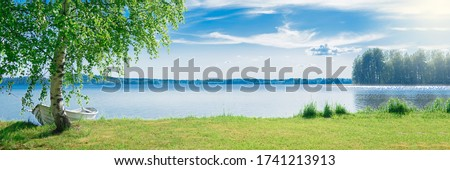 The beautiful landscape of a white simple wooden boat tied to a birch tree on the lake somewhere in the depths of Finland. Good summer day in nature. Concept vacation on the lake. Banner.