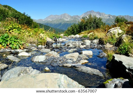 The beautiful landscape of pure mountain stream, washing the large stones,against the backdrop of high mountains