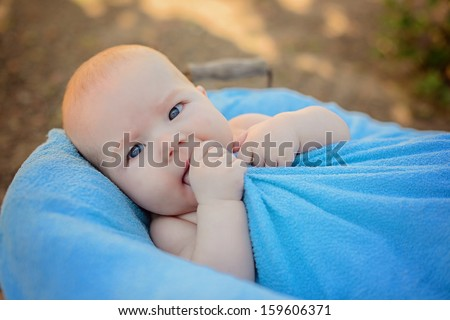 The beautiful little boy lying in a basket in a sunny day in park