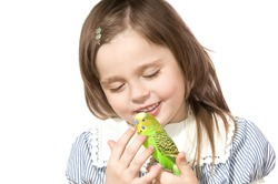 The beautiful little girl holds Parrot and smiles on white background close up