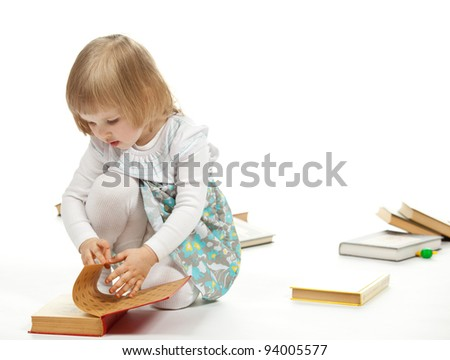 The beautiful little girl sitting among books and turning over the pages; white background