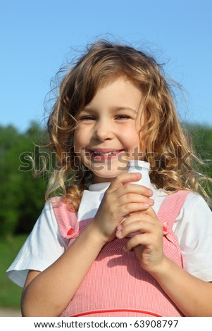 The beautiful little girl with a yoghurt small bottle, against wood and the blue sky.
