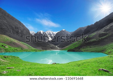 The beautiful mountain lake with a bright sun the sky