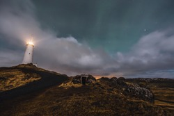 The beautiful northern lights or aurora borealis in Iceland with lighthouse near Keflavik named Reykjanes Lighthouse.