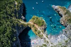 The beautiful rocky arch of arcomagno over a blue, clear, pristine sea