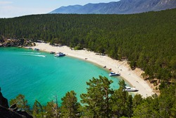 The beautiful sandy beach on summer sunny day. Lake Baikal, the Sandy Bay. Yachts near the shore, tourists sunbathe on the beach