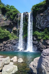 The beautiful scenic panorama view of Jeongbang Waterfall and blue water, A famous waterfall on Jeju Island that the only water fall in Asia that falls directly into the ocean. South korea.
