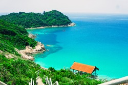 The beautiful scenic view of Small Perhentian Island in Terengganu, Malaysia. The wide view of ocean and green island from the peak of hill. The concrete stairs lead the way to the abandoned jetty.