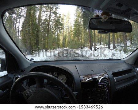 The beautiful scenic views of the huge granite mountains, tall green trees and snow on the road of Yosemite National Park during the winter through the windscreen window of a motor vehicle car #1533469526