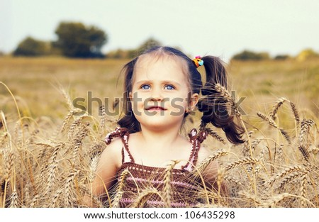 The beautiful small child play in the field