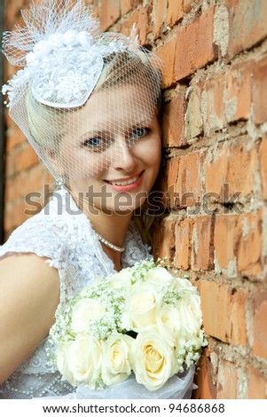 The beautiful smiling bride leaning against a wall and holding a bunch of flowers; wedding day