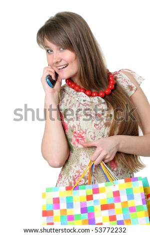 The beautiful smiling girl with purchases speaks by a mobile phone on a white background