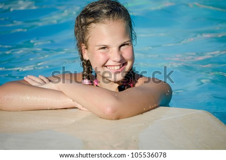 The beautiful smiling young  girl in pool