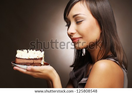 The beautiful smiling young woman with a cake