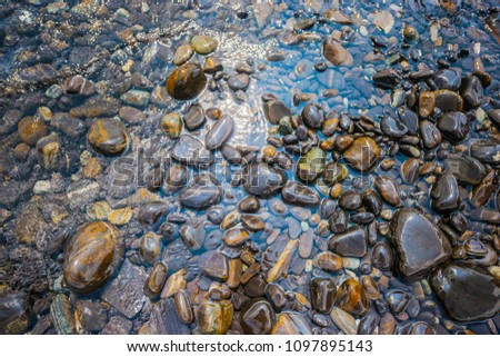 The beautiful stones island in Tarutao National Park. Stun. Hin Ngam Island of Asian heritage park and reserves. Koh hin ngam. Black pebble stones on the beach. Wet black stones. Rock island beauty
