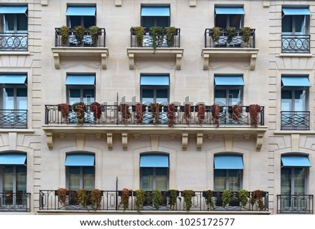The beautiful style of balconies and windows with flowers hanging, look retro . Concept Vintage balcony in Paris, France.  #1025172577