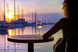 The beautiful woman drinking wine and watching a decline of sun