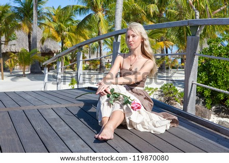 The beautiful woman in a long dress sits on the wooden bridge on the tropical island