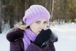 The beautiful woman on walk in the winter in cold weather