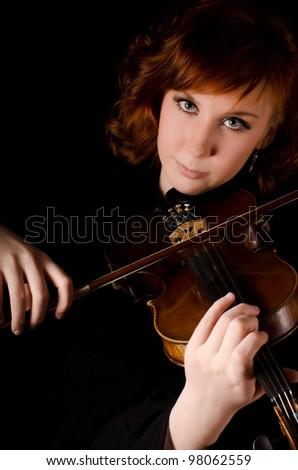 The beautiful woman plays violin on black
