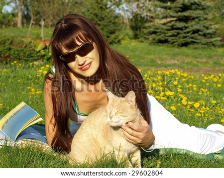 The beautiful woman the brunette in park with a cat
