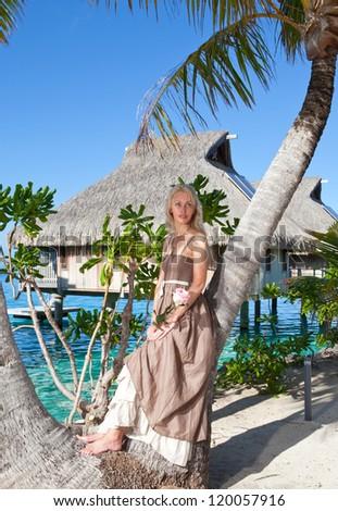 The beautiful woman with a rose at a palm tree. Bora-bora, Tahiti