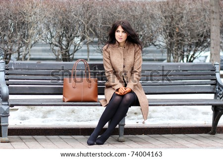 The beautiful young city woman sits on a bench
